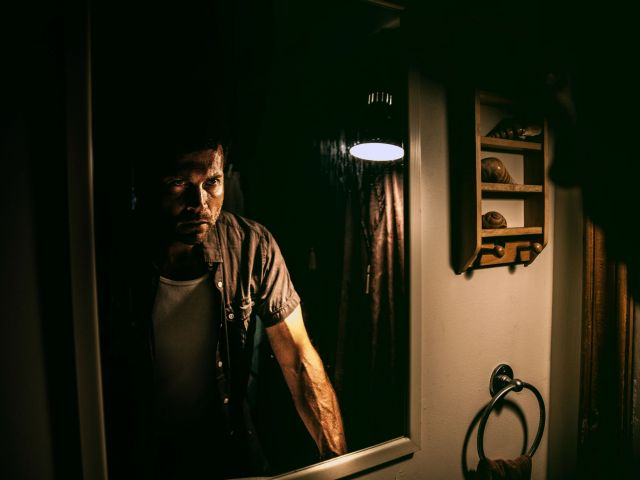 man standing in front of a mirror in the grips of a strong emotion